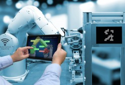 Industry 4.0 concept . Man hand holding tablet with performance check screen software and blue tone of automate wireless Robot arm in smart factory background